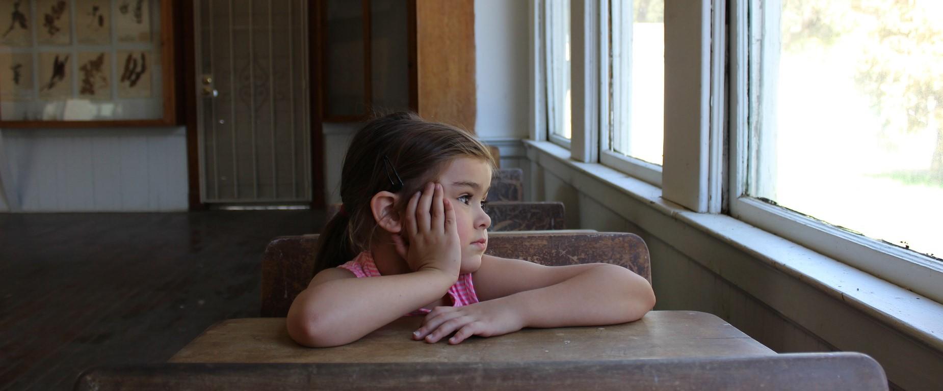Pieni tyttö istuu koulussa pulpetissa ja katsoo ulos ikkunasta.