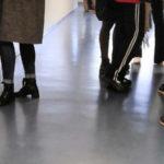 Kuvassa näkyy seisovien ihmisten jalkoja ja sääriä.