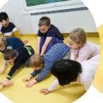 Kuvassa päiväkoti-ikäisiä lapsia leikkimässä lattialla.