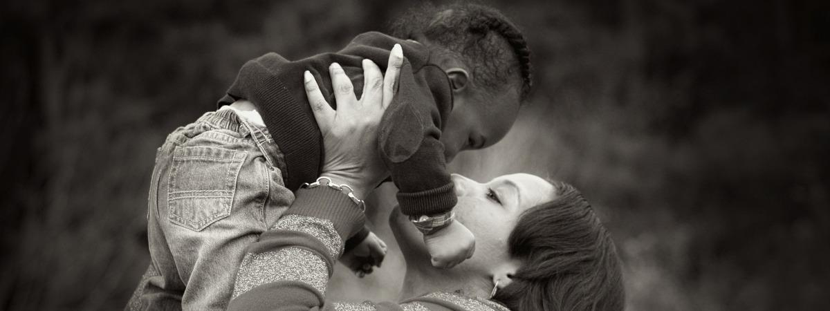 Nainen (äiti) nostaa pienen lapsen ilmaan omia kasvojaan vasten.