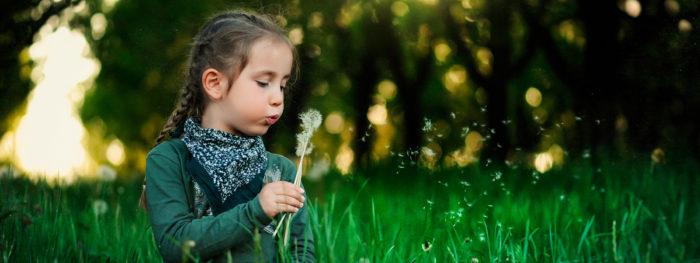 Lapsi puhaltaa voikukkaa vehreässä ympäristössä