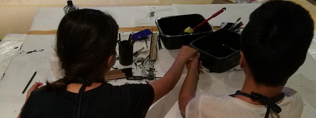 Kaksi nuorta maalaa pöydän ääressä
